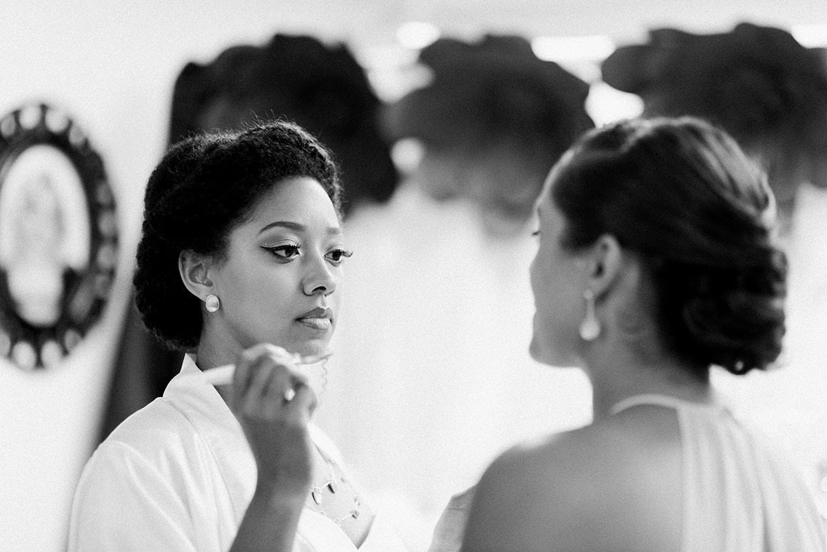 Bride and Bridesmaid adding final touches in the early morning