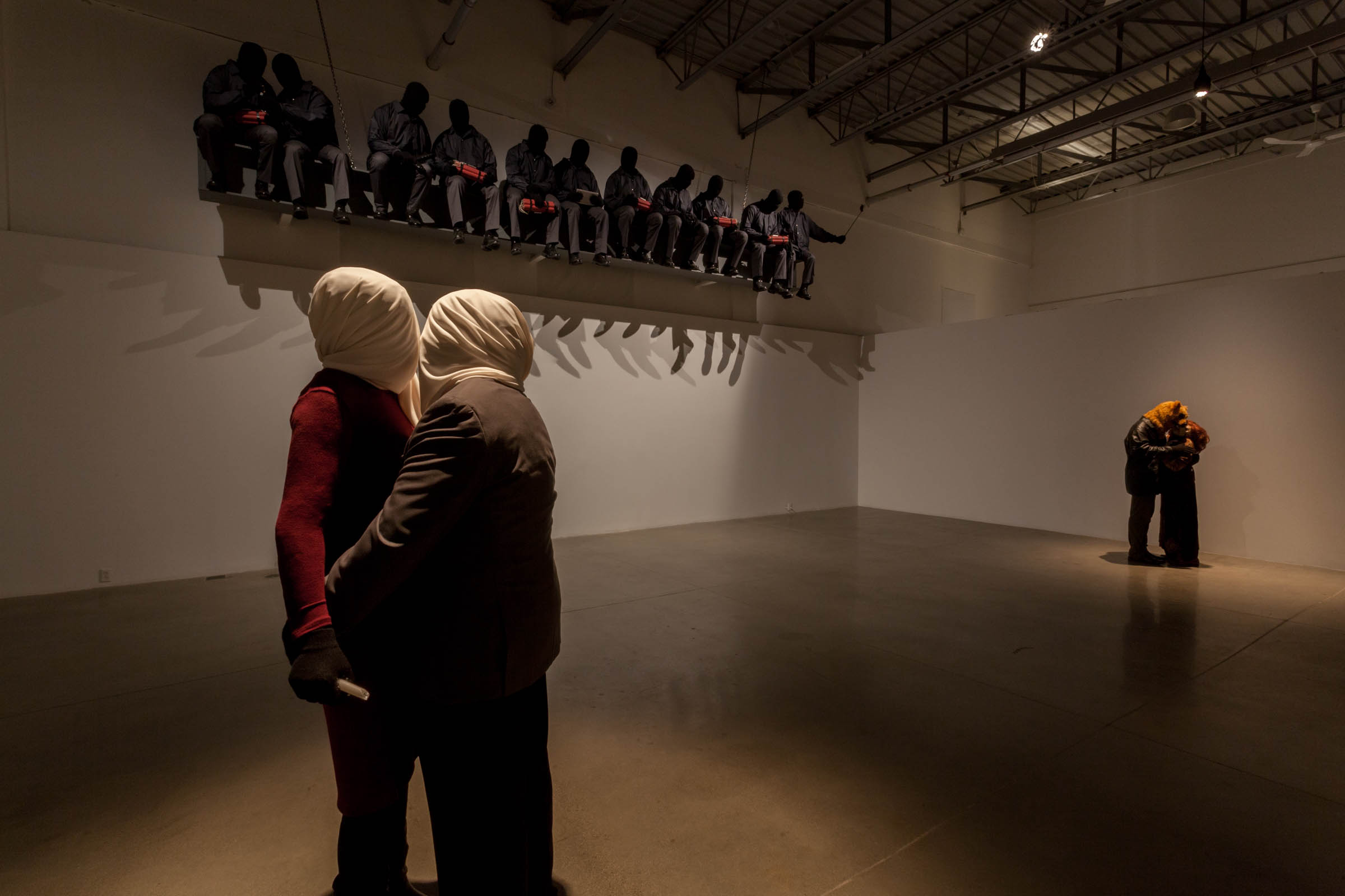 Mark Jenkins , Installation shot at Arsenal Contemporary Toronto, Foreground is  Below the Fold , 2016, Far right is  French Kiss , 2016. Top is  Suicide Bombers Atop a Skyscraper , 2016