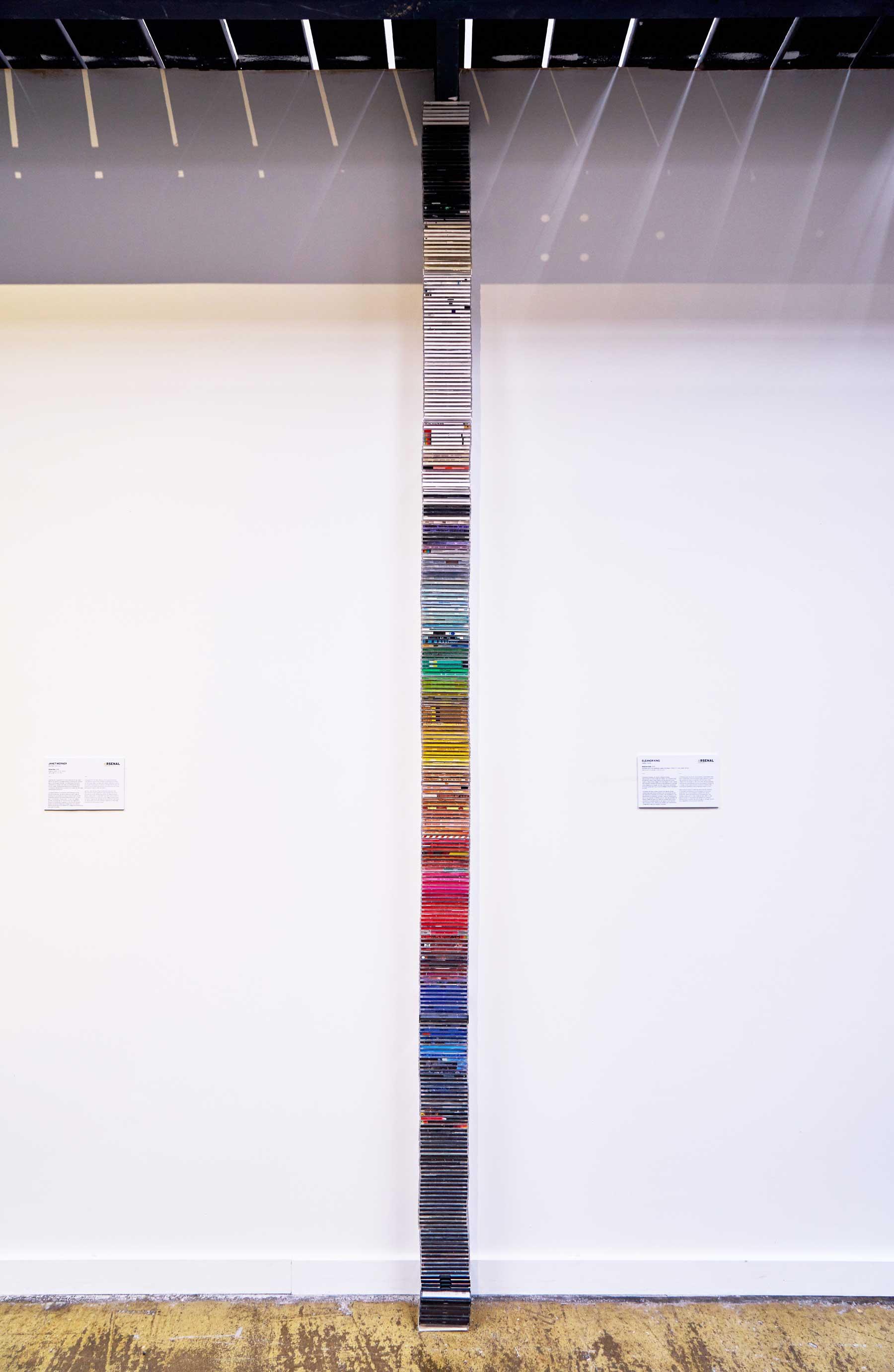 "Eleanor King ,  Redacted Stack , 2014, Plastic CD cases, paper, acrylic, 132"" x 5"" x 4 1/2"" (335,3 x 12,7 x 11,4 cm)"
