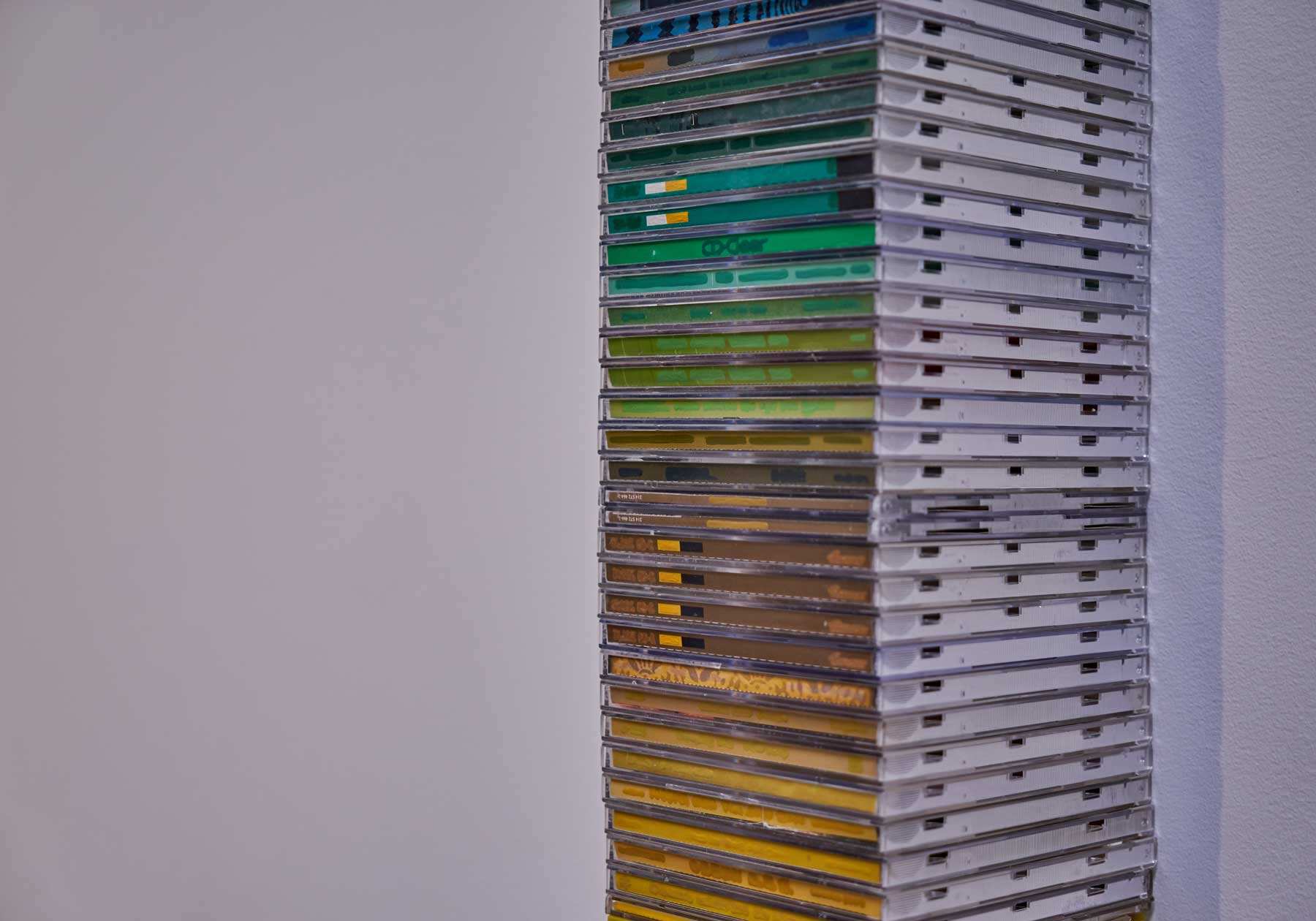 """Eleanor King ,  Redacted Stack , 2014, Plastic CD cases, paper, acrylic, 132"""" x 5"""" x 4 1/2"""" (335,3 x 12,7 x 11,4 cm) (Detail)"""