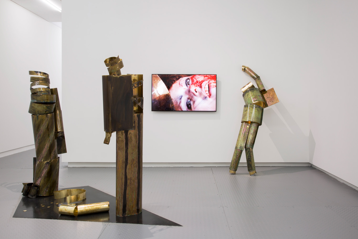 """Caroline Mesquita,   Green-dressed Woman  ,  2017, Oxidized brass with resin,  68"""" x 19"""" x 10"""";  The Young Businessman 2 , 2017, Oxidized brass with resin, 70"""" x 18"""" x 13"""";  The Ballad , 2017, Digital video with colour and sound, 29:00 min;  The Mechanic 2 , 2017, Oxidized brass with resin, 30"""" x 27"""" x 53"""", Courtesy of carlier 