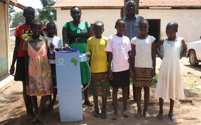 A group of Kenyan school children and their teacher stand with the water filter that is going into their classroom!