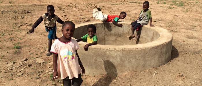 Village children play in and around an empty well.