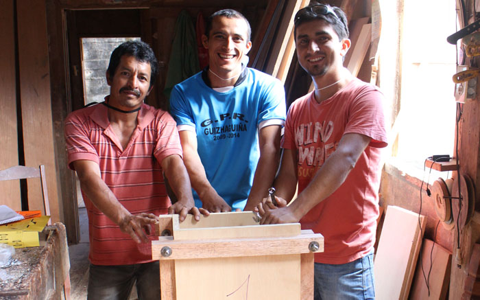 Jose, Fabian, and Johnathan stand proudly behind the Wood Mold they built together.
