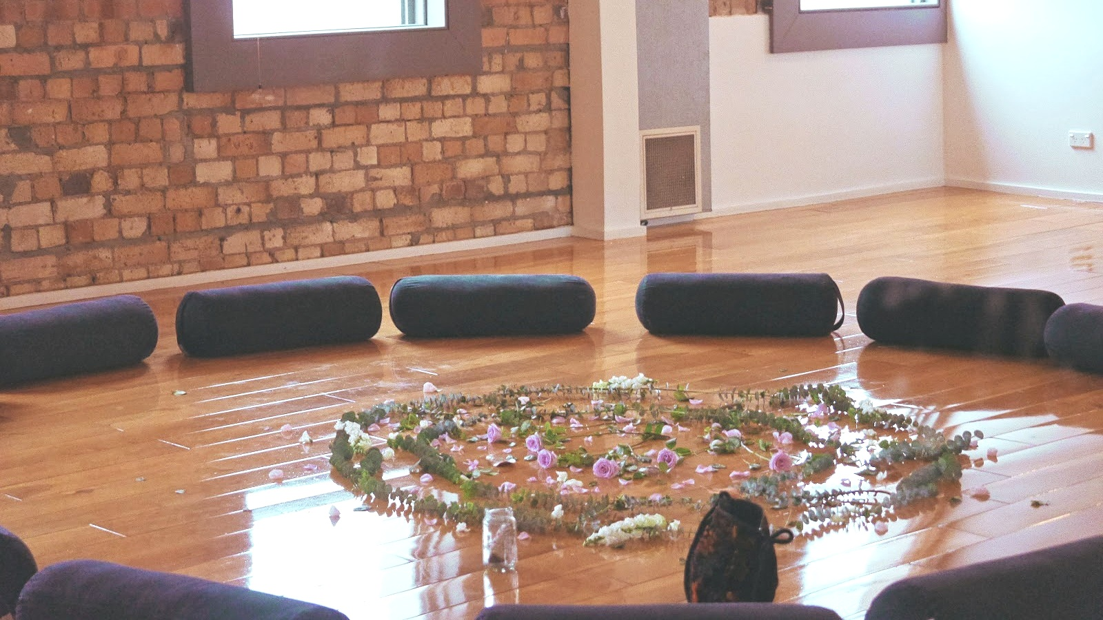 Kaity's beautiful studio for breath-work - mats arranged in the circle around a bunch of wonderful flowers