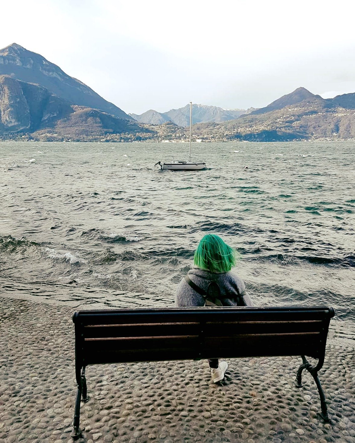 Penny sitting on the bench looking out to a wonderful mountain and water view