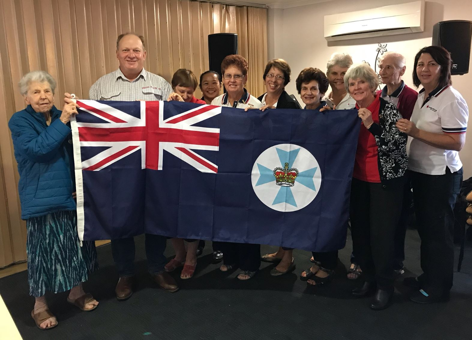 Shane Knuth handing over the State Flag to the Kurrimine / Silkwood Red Cross Branch for Queensland Day. He also enjoyed a few games of Hoy while there!