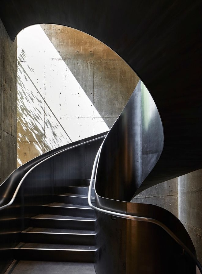 A spiral raw steel staircase connecting the four floors