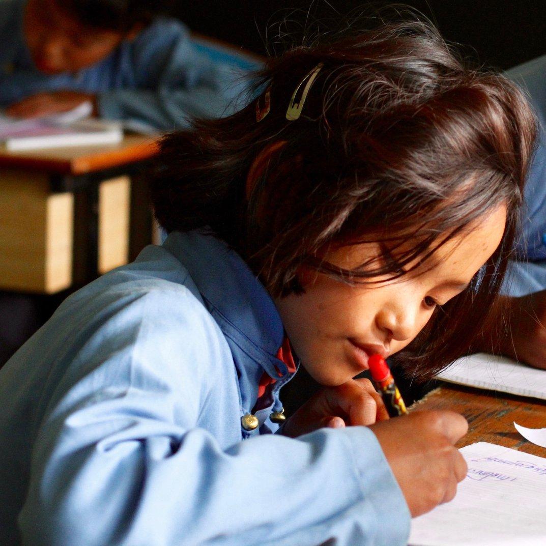 Student practices her Tibetan writing