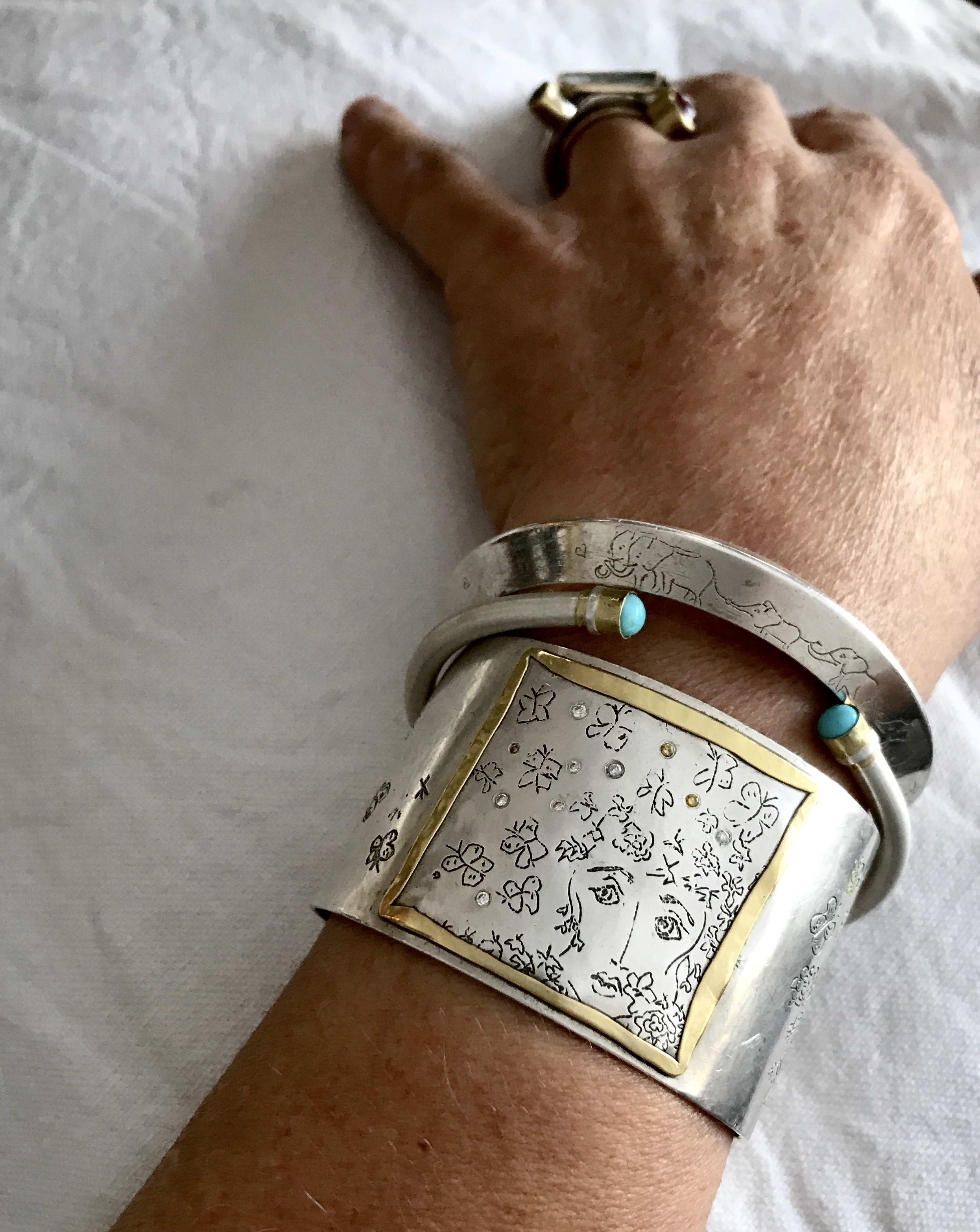 """My wrist on a typical day with my self-portrait titled """"losing my mind, or in my creative space"""""""", along with two others. . . the other wrist is equally adorned. circa 2019"""