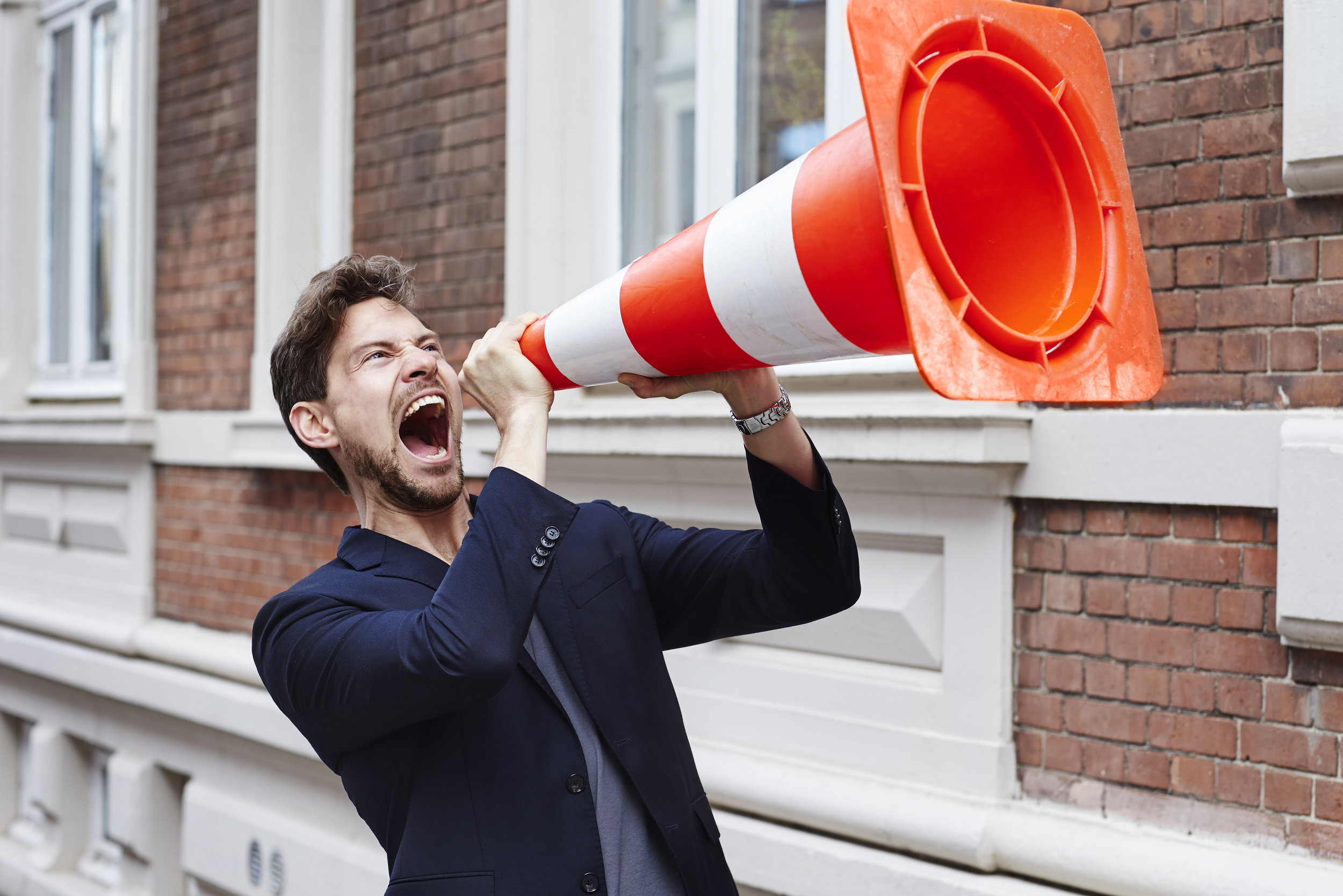 Guy holding traffic cone and making himself heard