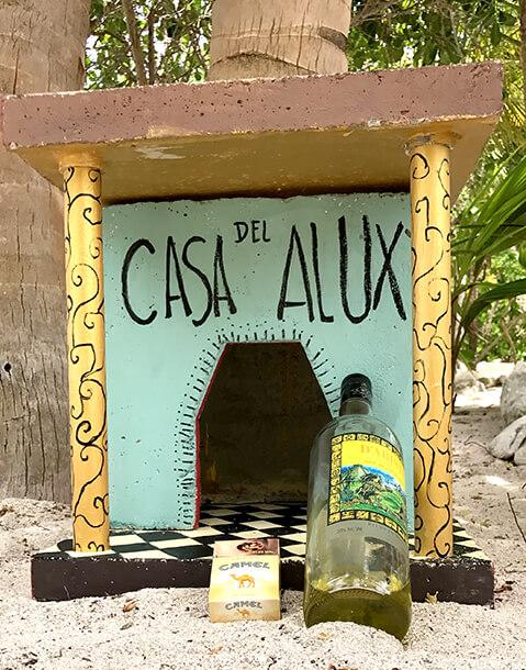 La casa del Alux - La gente les deja ofrendas en forma de caramelos, tabaco y alcohol para que les cuiden los sembradíos y les construyen pequeñas casas o templos para que les permitan edificar.