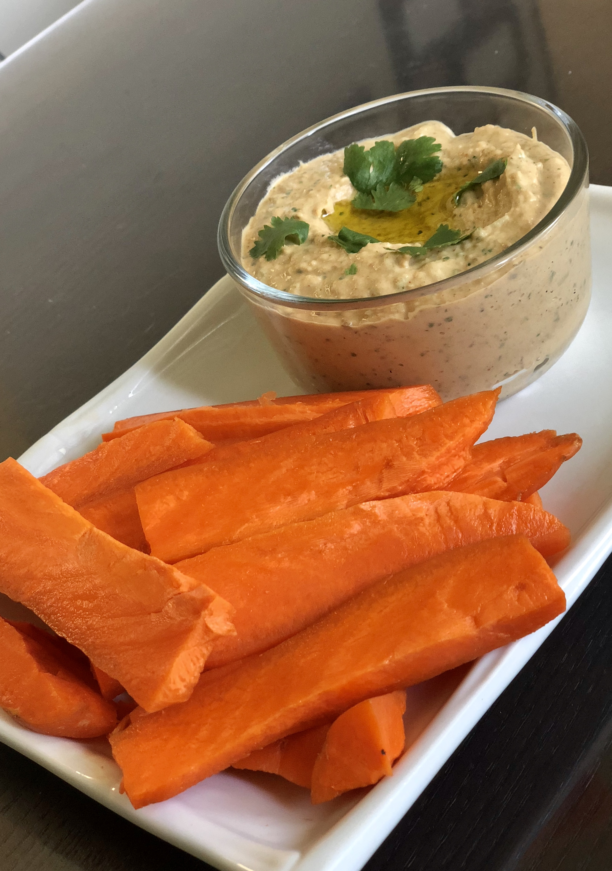 Garlic Hummus - 4 cloves of garlic 4 tablespoons of olive oil 1/2 cup of chopped cilantro 1 tablespoon of lemon juice2 cans of garbanzo beans half drained1/2 cup of tahini1/2  tablespoon of Mediterranean spice sea salt McCormick gourmet1/2 a tablespoon of paprika1/2 a tablespoon of basil 1/2 a tablespoon of oregano Directions:Put the oil, lemon, cilantro, and the cloves of garlic in and blend till the garlic is minced very small. Add the garbanzo beans, tahini, and the seasoning into the food processor.  Put the hummus in an air tight container and place it in the fridge to set. Consume with in 7 days.