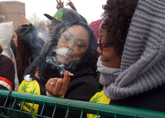 Kennya Anderson of Chicago passes a joint to her friend as marijuana smoke trickles from her lips during the Denver 420 rally. (Photo: Trevor Hughes, USA TODAY Network)