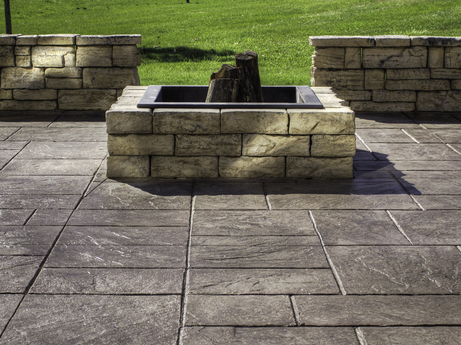Stunning-Stamped-Concrete-Patio-with-Interesting-Flooring-and-Square-Firepit-near-Wide-Grass-Yard.jpg