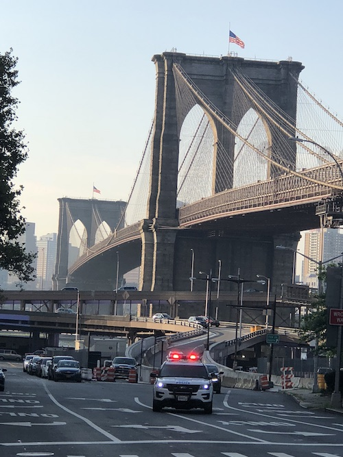 Police car with lights on driving by bridge in NYC.jpg