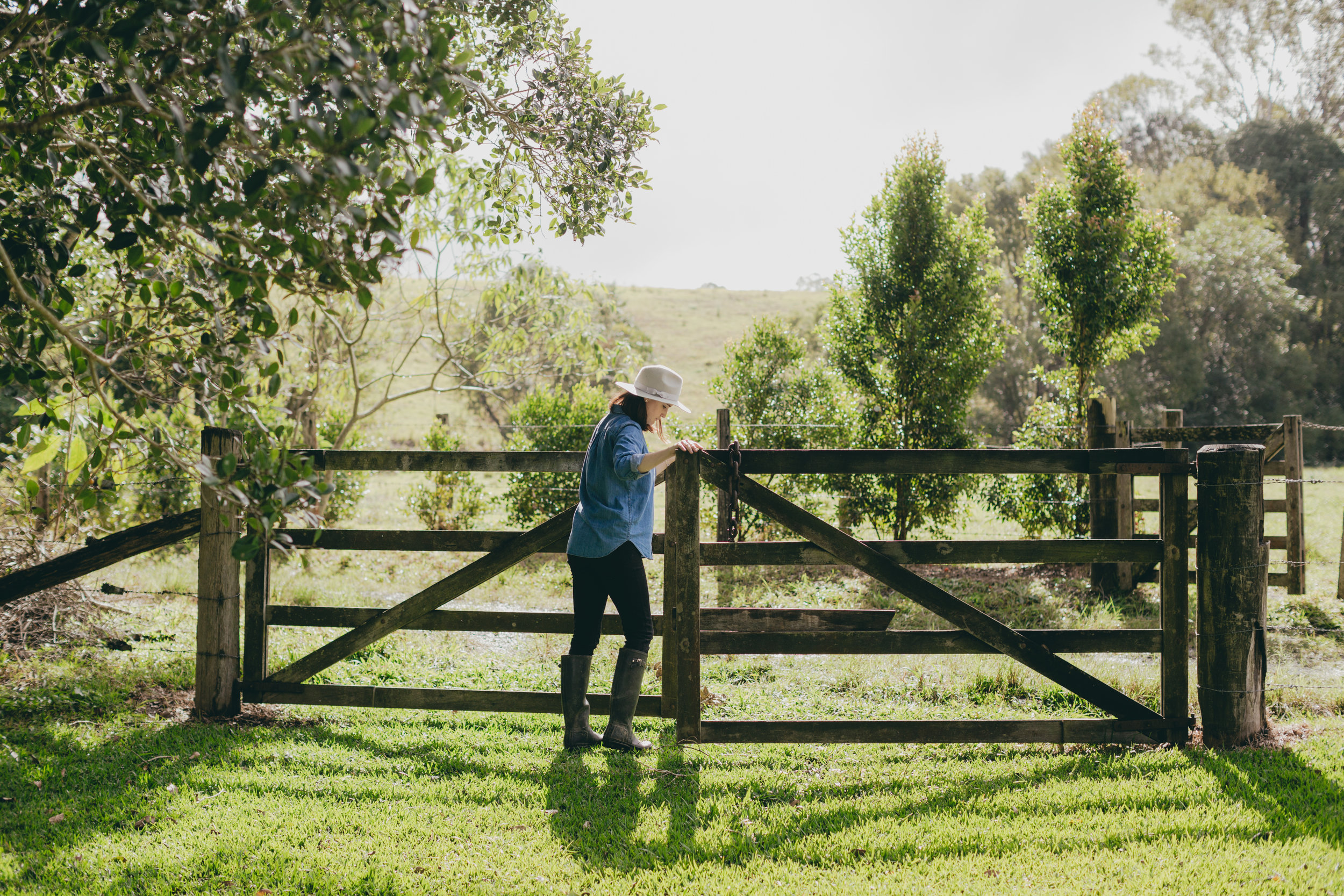 Rustic wooden gate being opened by farm worker.