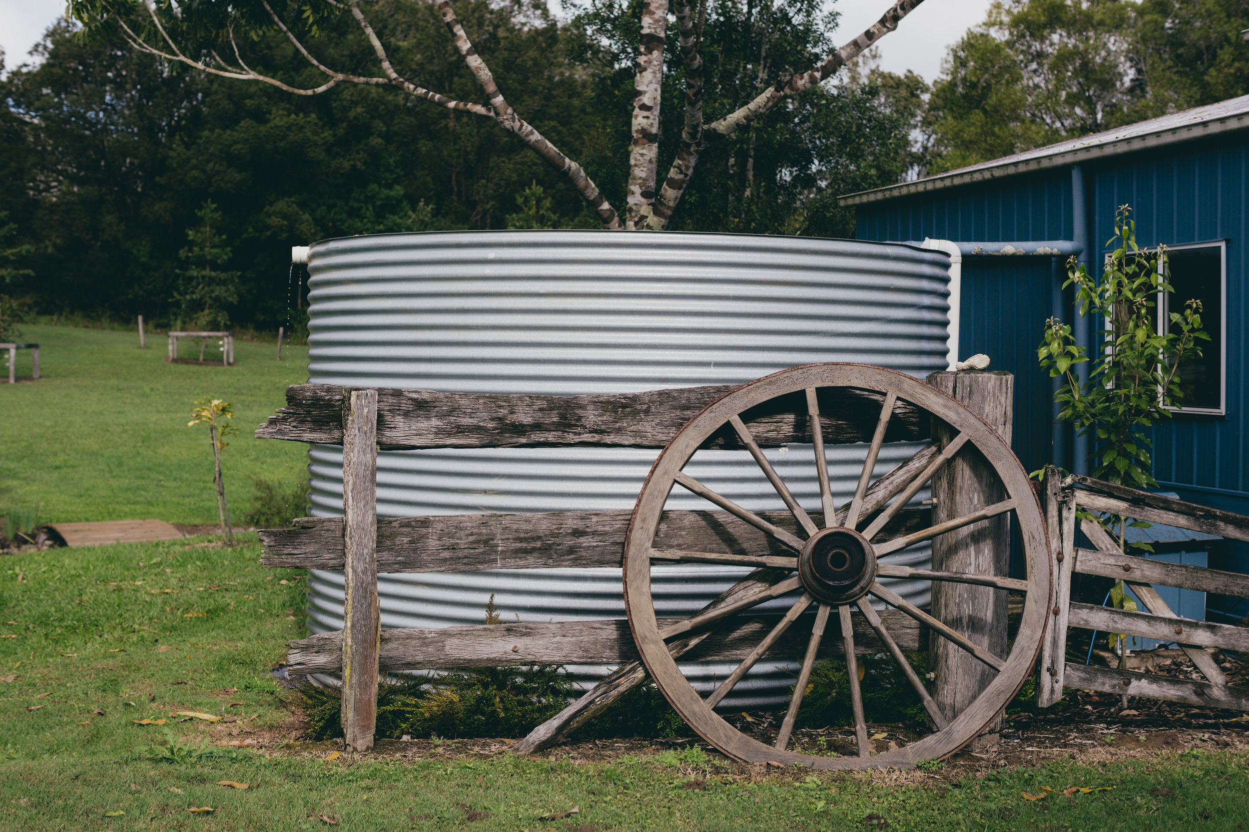 Water tank fenced with wooden slats, old wagon wheel leaning against the fence.