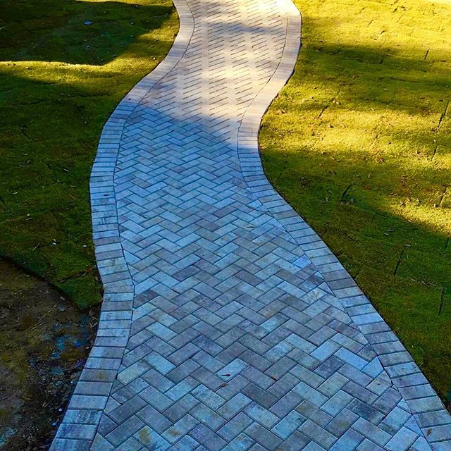 We've made walking from the front door to the side walk an enjoyable experience with this custom walkway. #pavers #frontyard #landscapedesign
