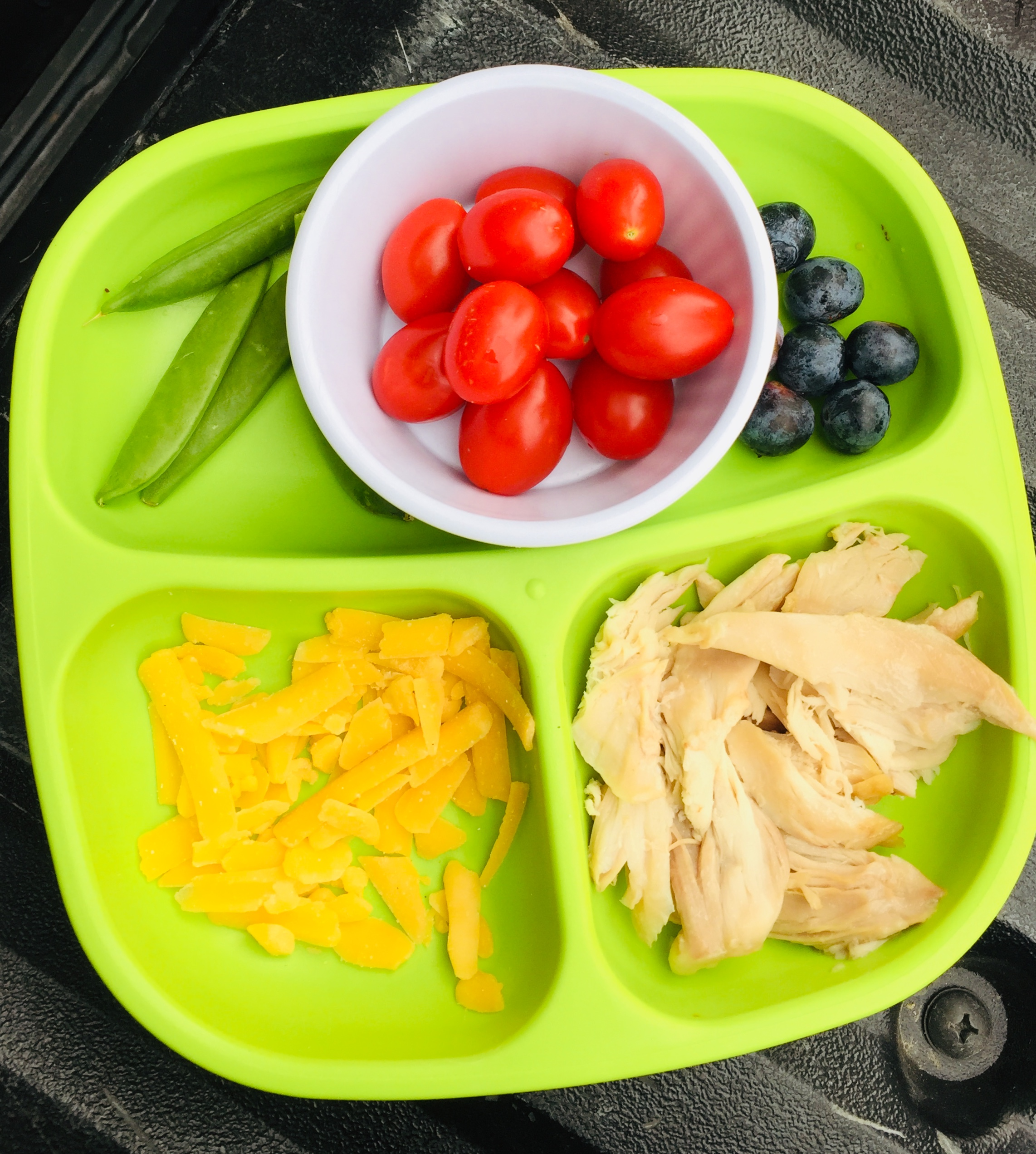 Snap peas, cherry tomatoes, blueberries, cheese and chicken.