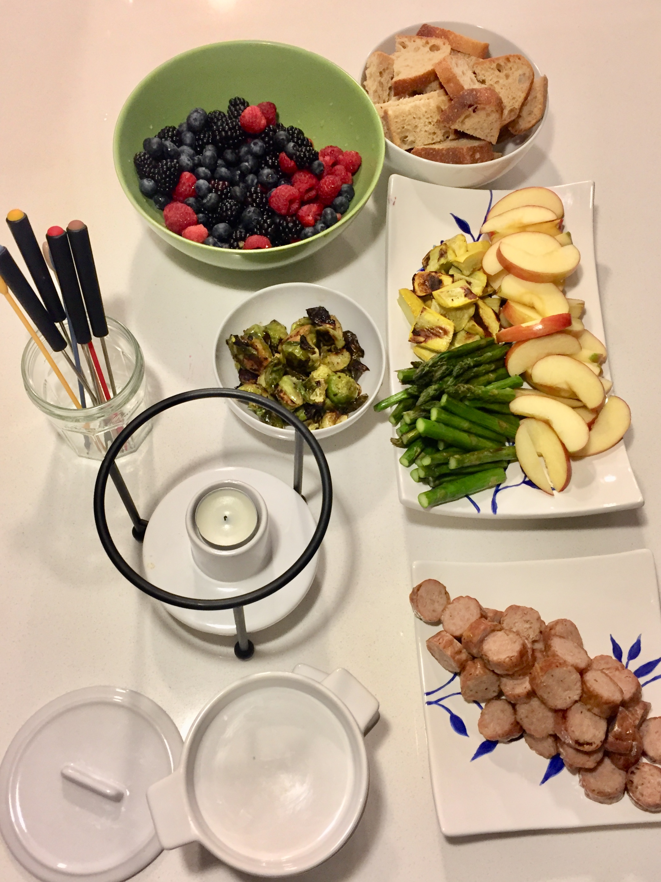 Fondue: Berries, whole wheat bread, apples.  Asparagus, brussels sprouts, yellow zucchini, and sausages (on the grill) and of course cheese fondue (not in the picture).