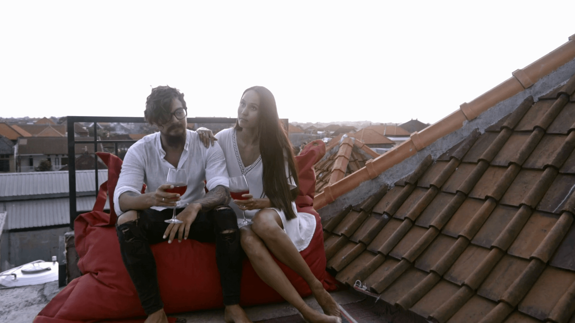 videoblocks-romantic-young-couple-sitting-on-rooftop-terrace-at-sunset-drinking-red-wine-smiling-and-speaking_rwmsa5nvm_thumbnail-full01 (1).png