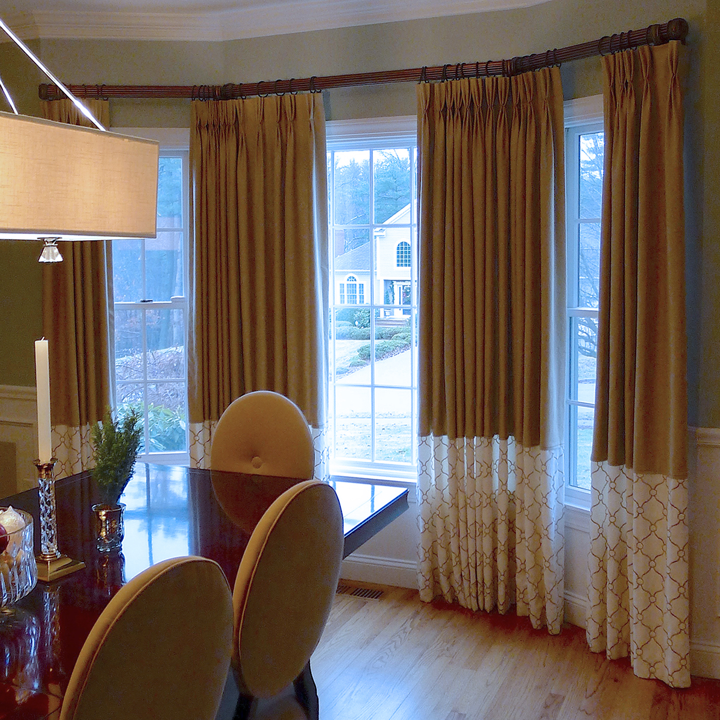 Color-blocked draperies - Custom-fitted drapery hardware and pleated drapery panels highlight a large bay window.