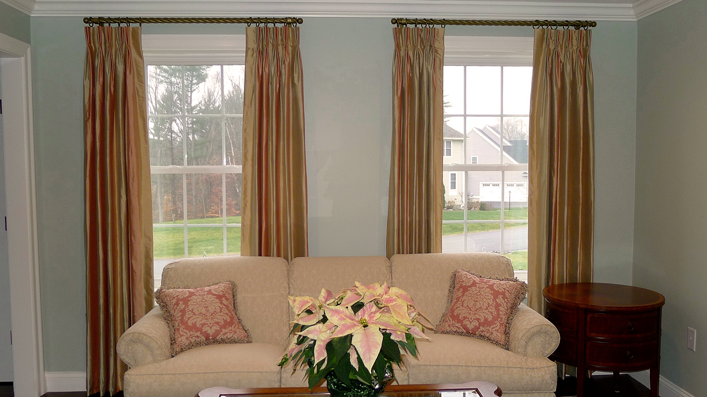 Choosing a unique drapery hardware such as twisted iron rods (above) makes a living room special.