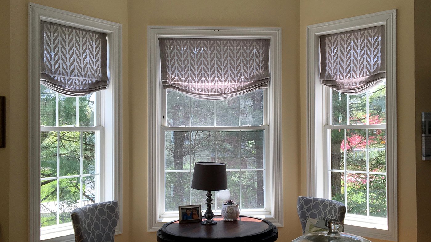 Stationary relaxed roman shades add softness to this family room.