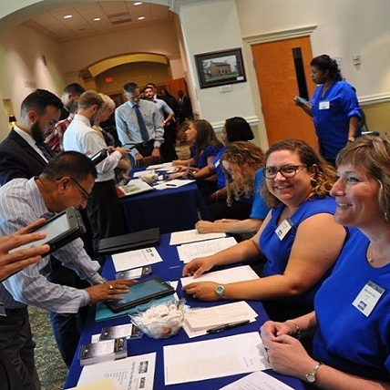 Women at table for job fair with one visitor