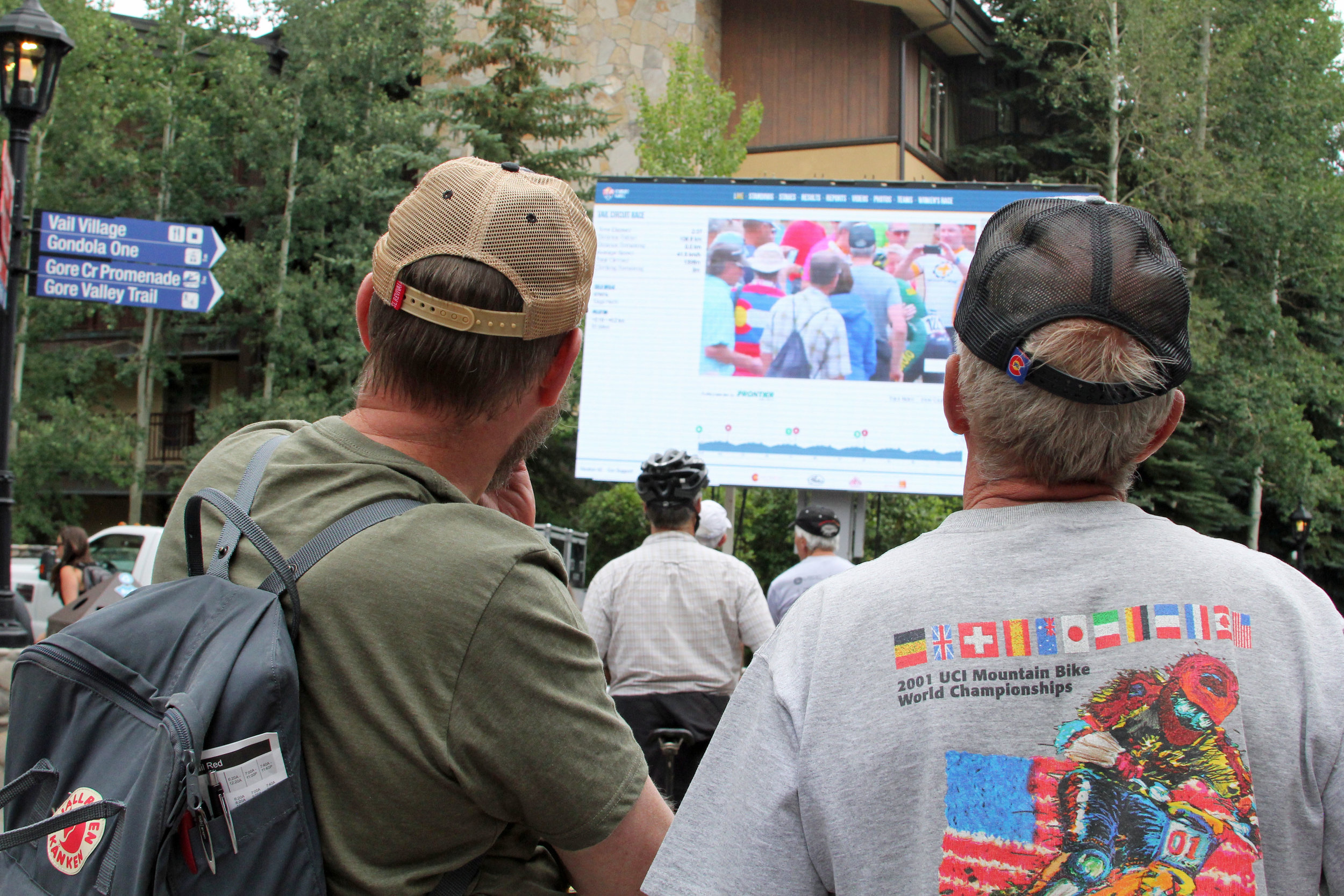 Spectators follow the 2018 Colorado Classic via a live stream displayed at the finish line.