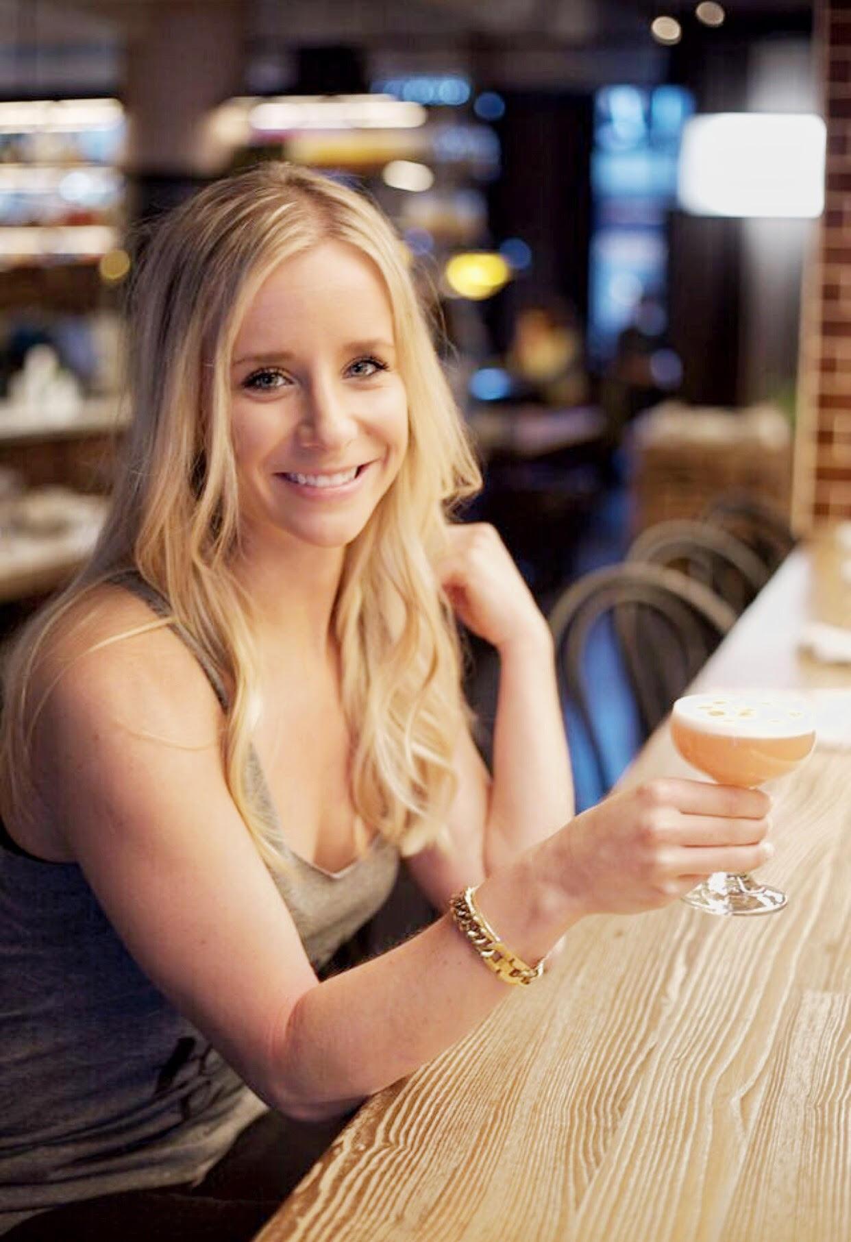 megan holding drink at bar