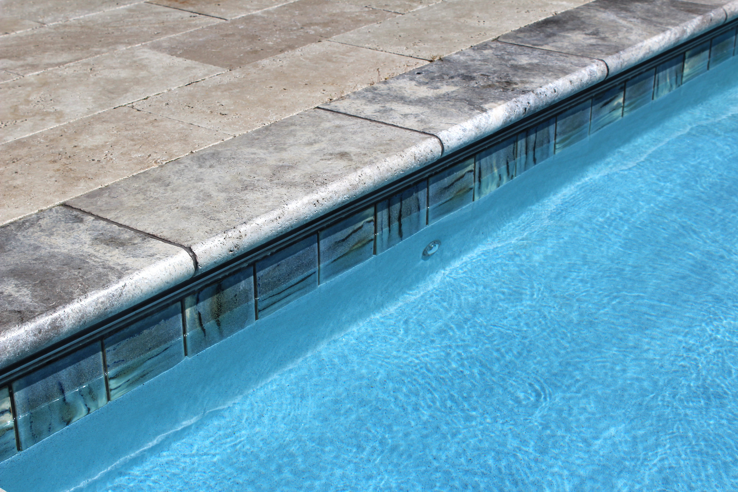 Tile & Coping - Porcelain Border TileBeautiful porcelain tile is installed at the water line on gunite and gunite-steel hybrid pools. We offer a wide variety of colors and styles from Fujiwa Tile, Artistry in Mosaics and Lightstreams Glass Tile to bring yourBullnose Travertine CopingTravertine is used for its aesthetics and functionality. It's available in multiple shades and with varying degrees of contrast. It's also a durable, low maintenance stone that stays cool on the feet, absorbs water and has a non-slip surface. Travertine is a great option for the pool deck as well.