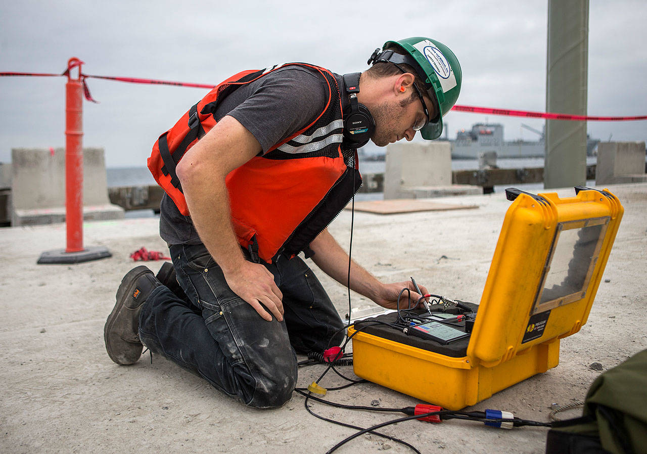 Acoustical engineer Justin Morgan writes down sound measurements during construction at the Port of Everett. (Olivia Vanni / The Herald)