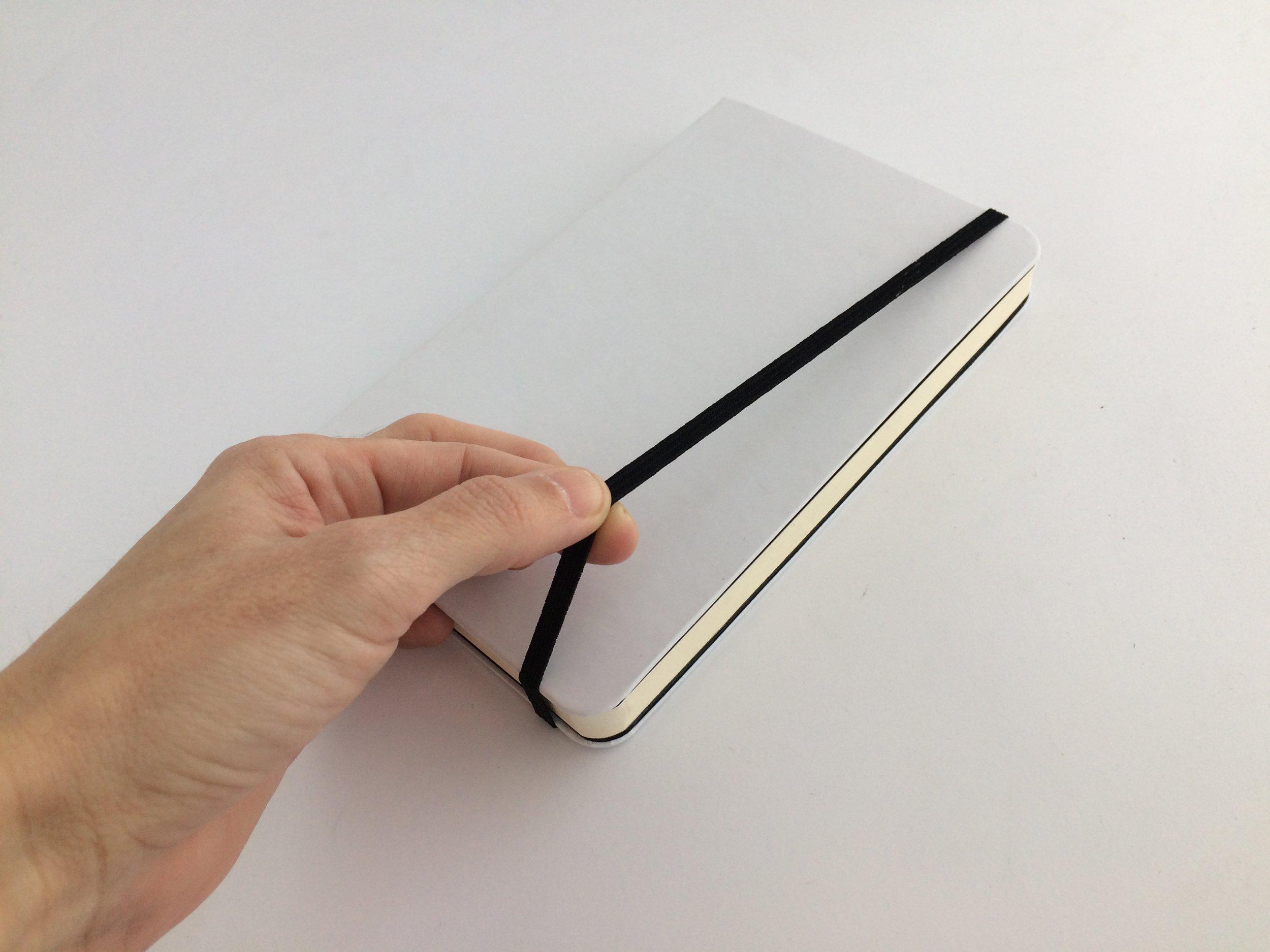 Resorte para cerrar la libreta. Disponible en negro o gris claro.