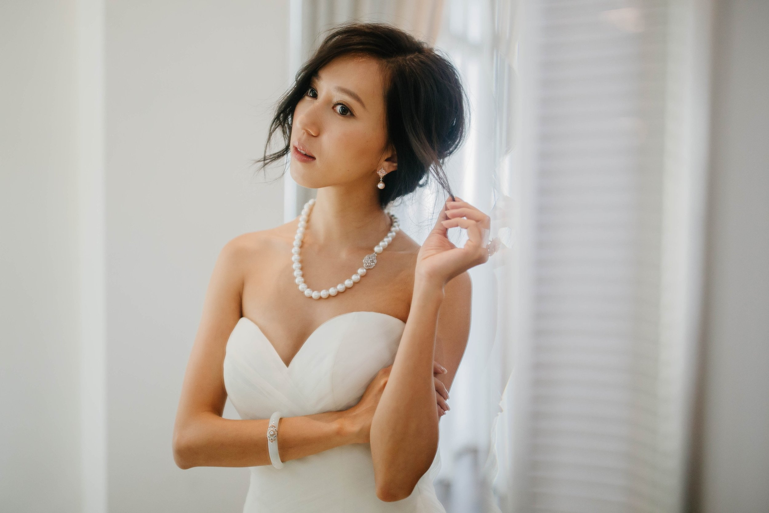 For the Glam Bride - Left,Melissa wears the lavish White South Sea Pearl Necklace with Peranakan Clasp, a piece that captures light perfectly, with its full string of lustrous pearls, moonstones and intricate metalwork inspired by tasteful Peranakan lacework. The South Sea pearls are set in White Gold, made for classy elegance. The look is completed with the Bamboo Marquise Ringin iridescent White Quartz and the captivating Peranakan Lace Jade Bangle.