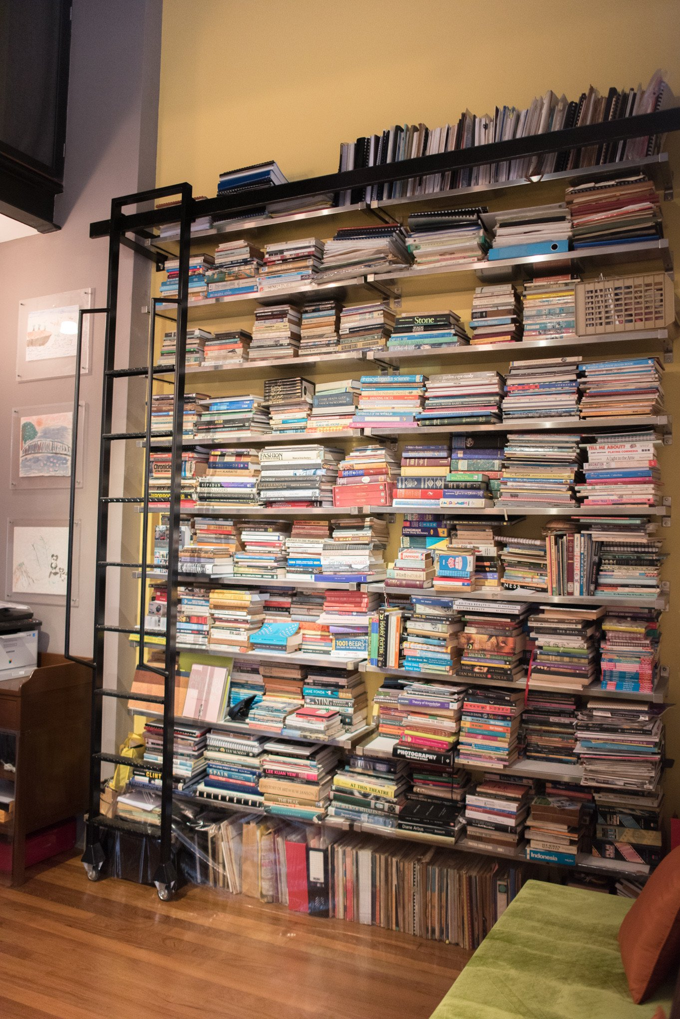 The wall of learning and mementoes in a cosy reading room. The top shelf is a treasure trove of scripts from Kheng Hua's different roles.