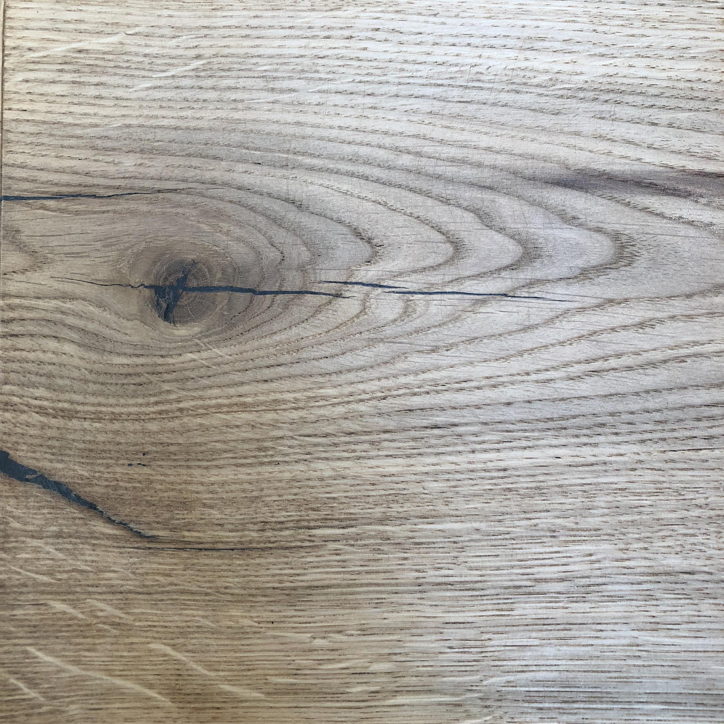"""Eichenholz - Die Eiche zählt zu den Harthölzern. Ihr langsames aber stetiges Wachstum verleiht dem Holz seine Dichte und Härte. Die Auswahl des Holzes erfolgt auch hier auf entgegengesetztem Weg zur herkömmlichen Holzindustrie. Wir bauen darauf, dass wir dem Holz durch die Aufbereitung von """"Macken"""" eine Persönlichkeit verleihen, die bei standardisiertem Holz nicht zu finden ist. Eiche ist farblich von gelb- bis honigbraun einzuordnen und zeichnet sich durch besondere Maserungen und sogenannte """"Spiegel""""aus, welche im Bild besonders links unten als weiße Striche zu sehen sind."""