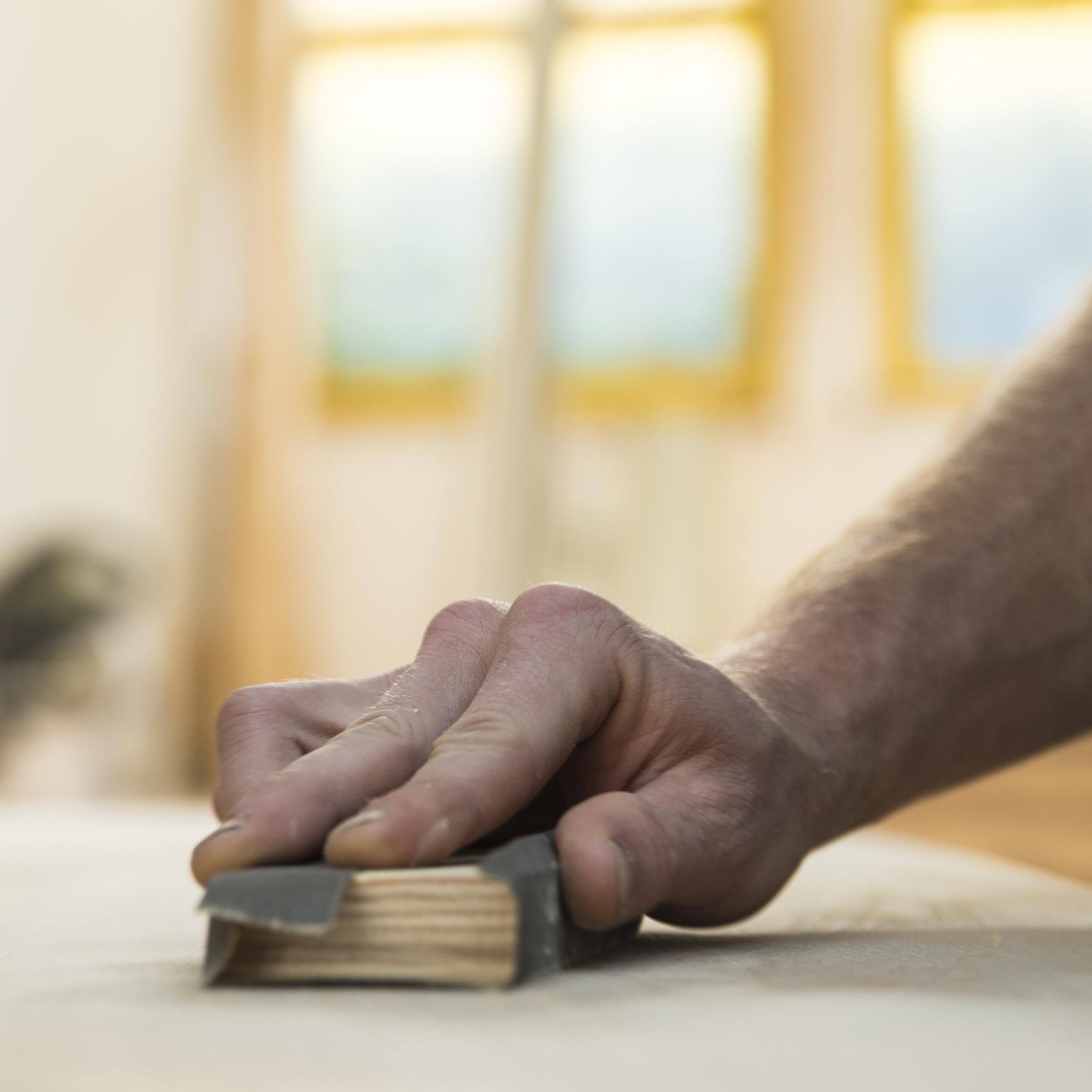 Schritt 2: - Wenn die Oberfläche wieder getrocknet ist, wird das Schleifpapier der Körnung 240 um den mitgelieferten Block geknickt um eine glatte Fläche zu erhalten. Nun die betroffene Stelle leicht anschleifen, dabei darauf achten, dass in Faserrichtung (Wuchsrichtung) des Holzes geschliffen wird.