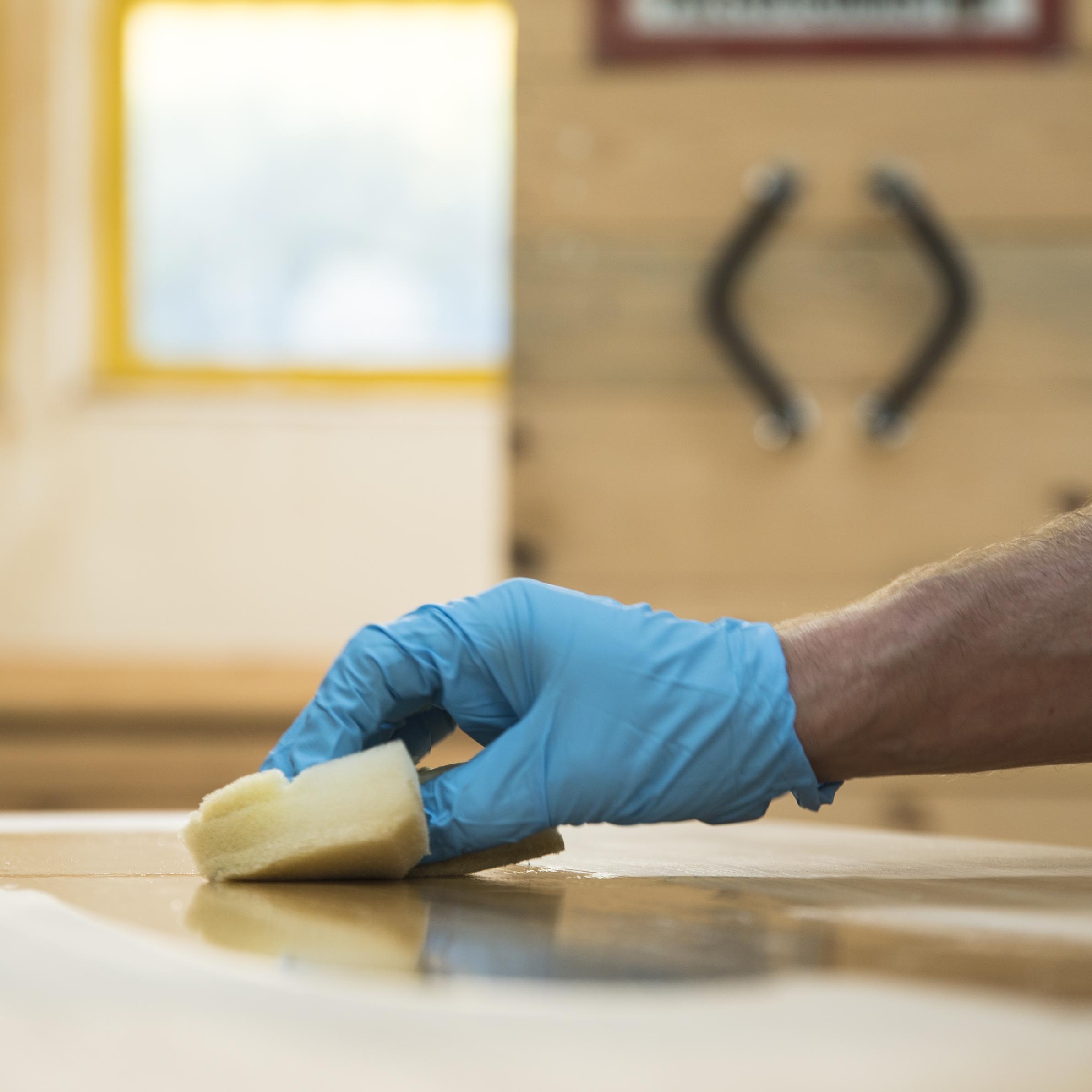 Schritt 4: - Handschuhe anziehen und mit dem Schwämmchen das Holzwachs auf die gewünschte Stelle auftragen. Darauf achten, dass nicht zu viel Holzwachs verwendet wird und das Holzwachs in Faserrichtung aufgetragen wird. Zum Schluss, falls vorhanden, das überschüssige Holzwachs mit dem Schwämmchen wieder abnehmen.