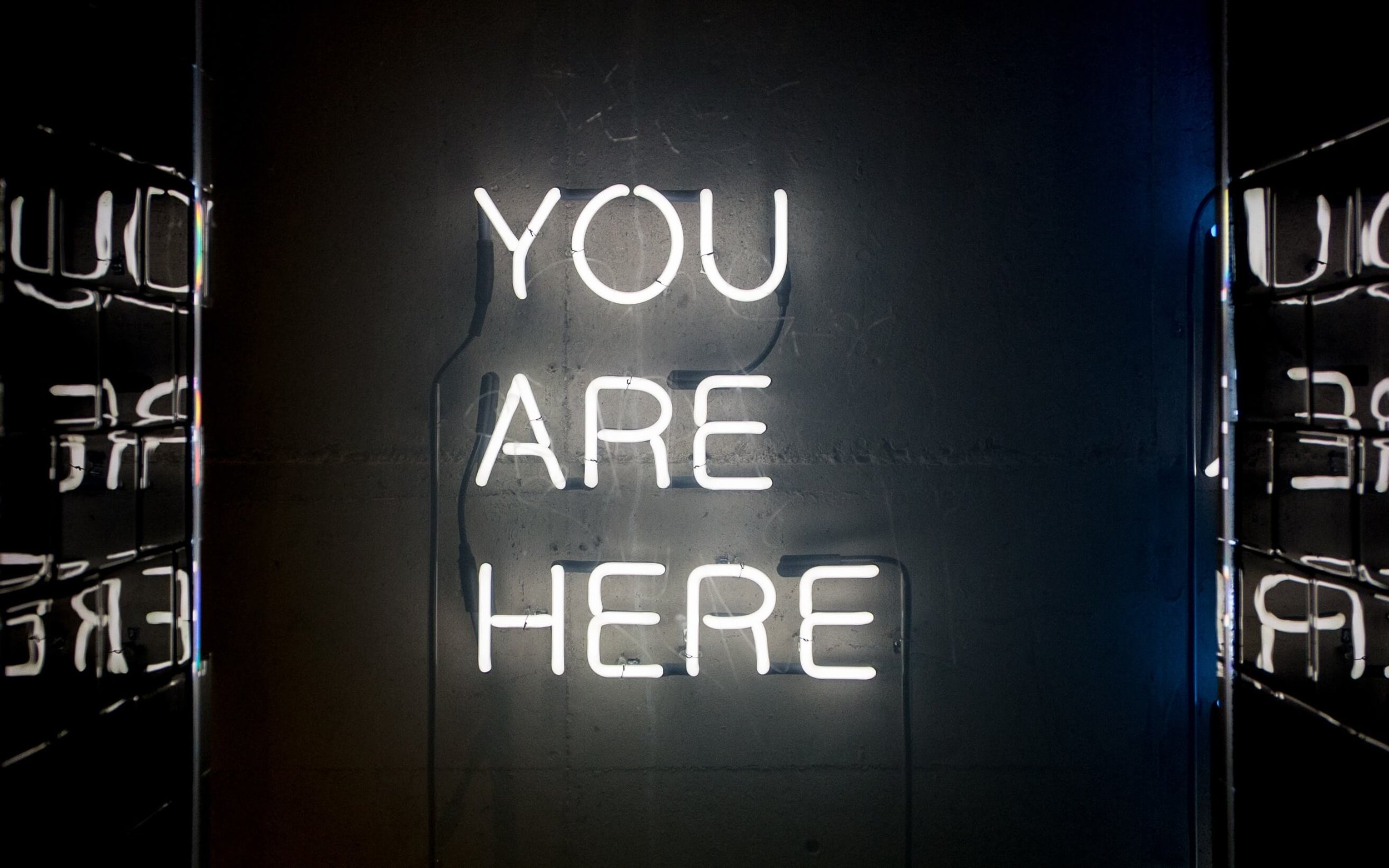 Neon sign saying you are here