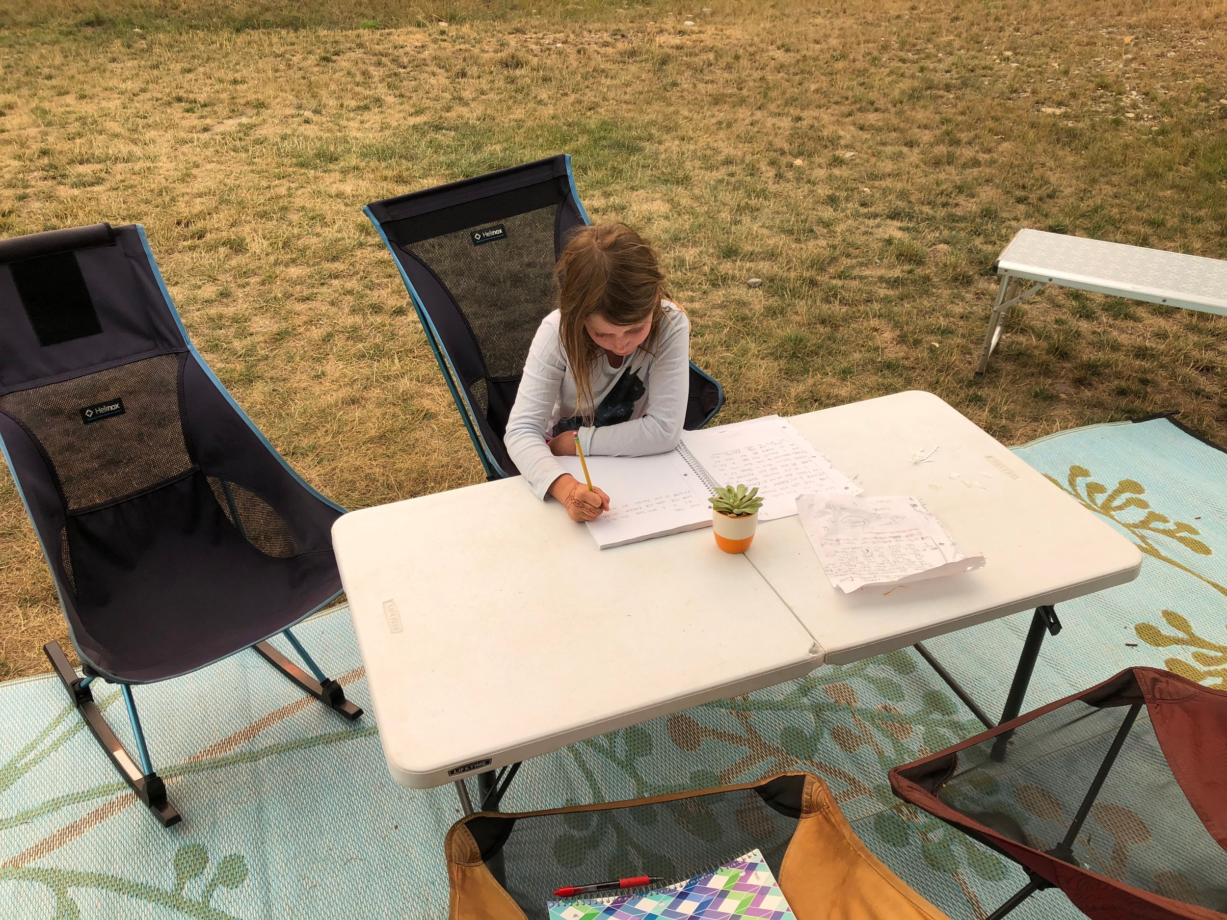 Isla at camp doing schoolwork