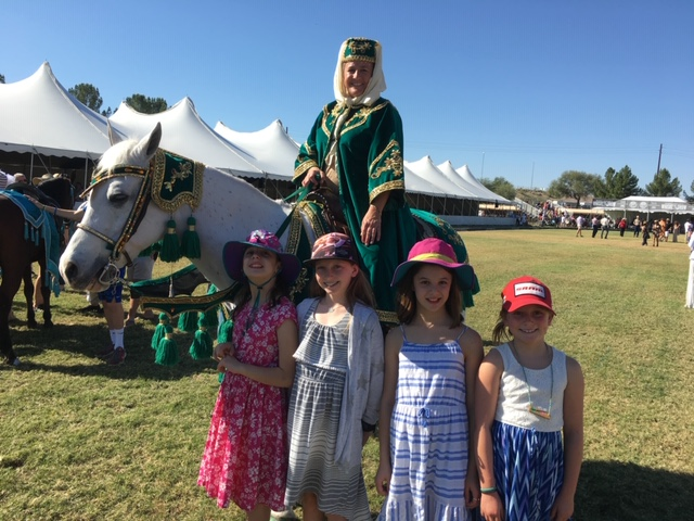 The little ladies posing with an Arabian horse and rider.