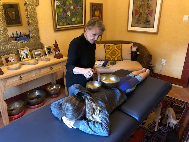 """Ellie getting a singing bowl therapy treatment from the owner (Sha Brown) of the city apartment we stayed in. Sha became so much more to us then just a """"landlord"""". Her openness to our family, and our girls, was sincere and heartfelt form the very beginning and her generosity went above and beyond. We miss her already!"""