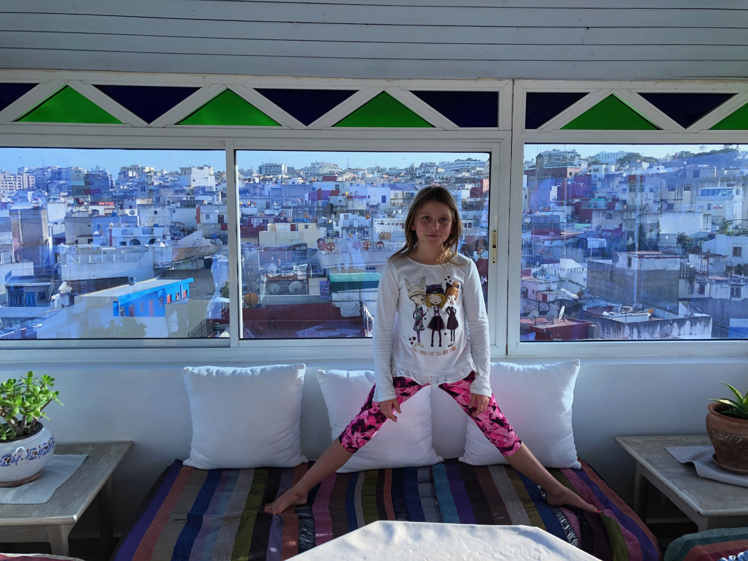 Isla on the roof of our riad with the medina in Tangier behind her