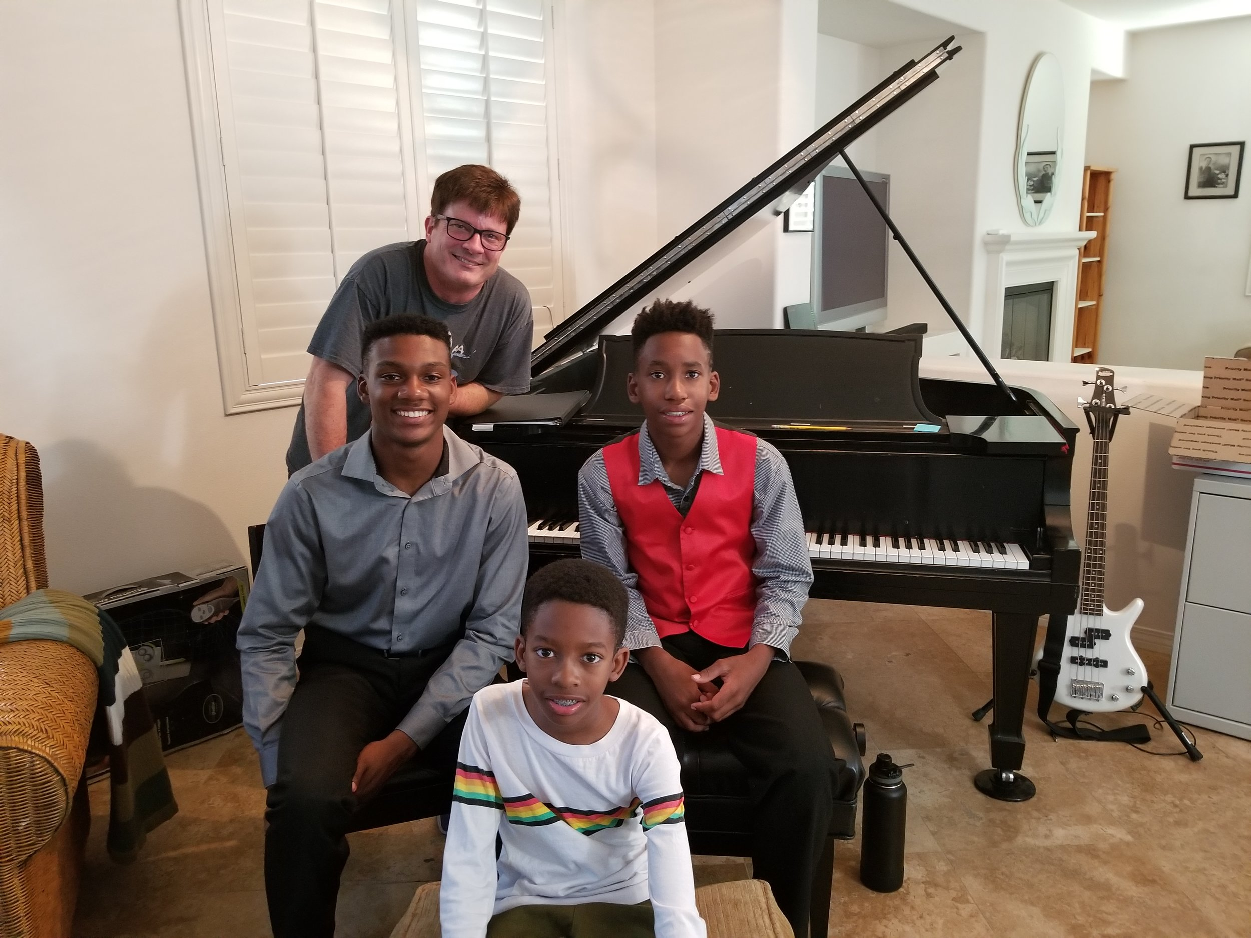 Siblings taking piano lessons in music studio