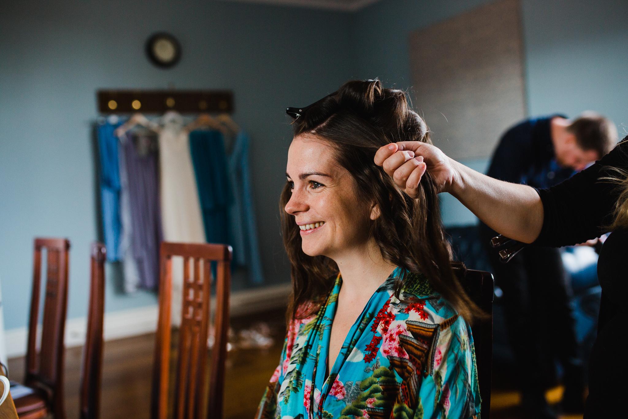 bride smiling having her hair done
