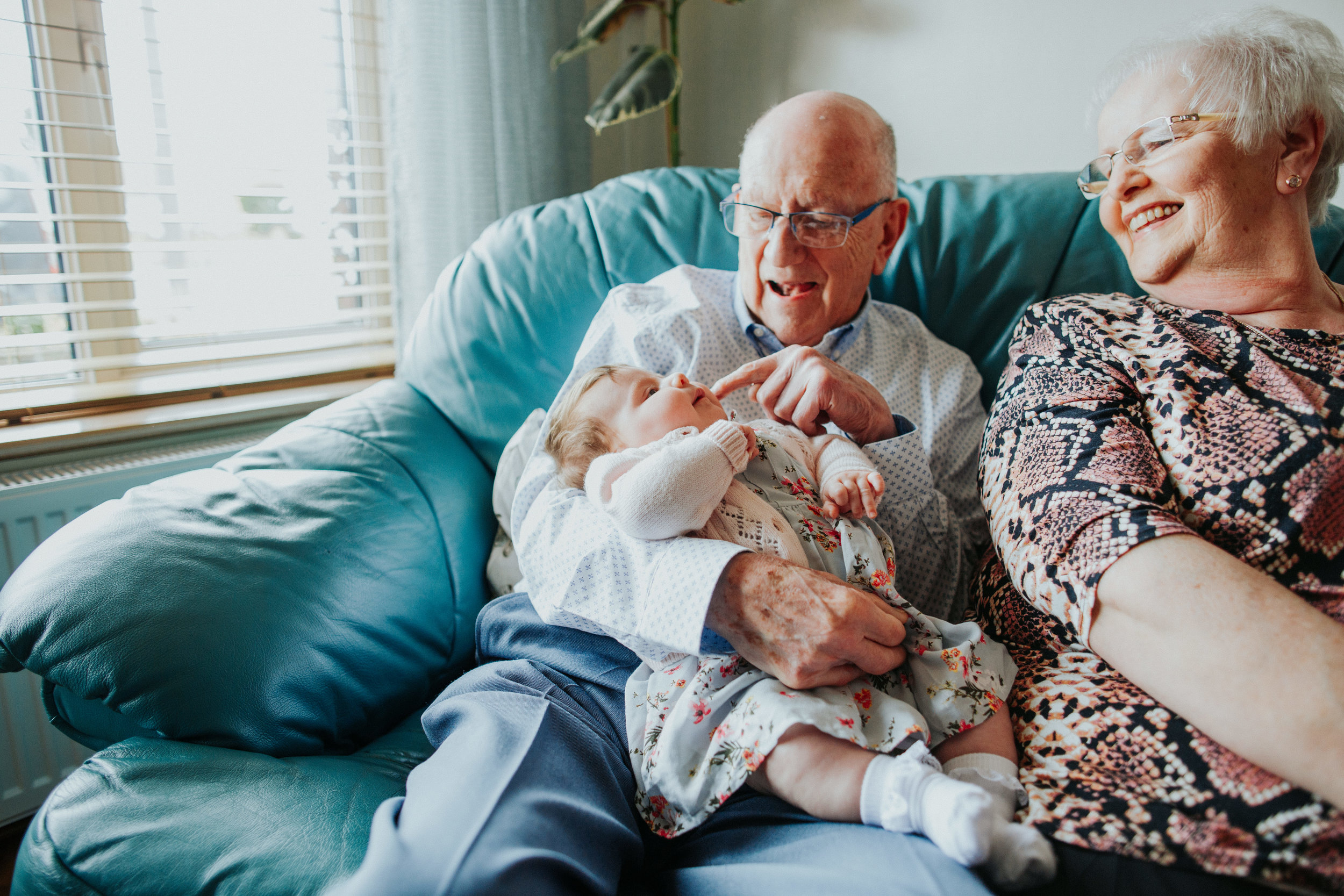 grandparents holding baby granddaughter