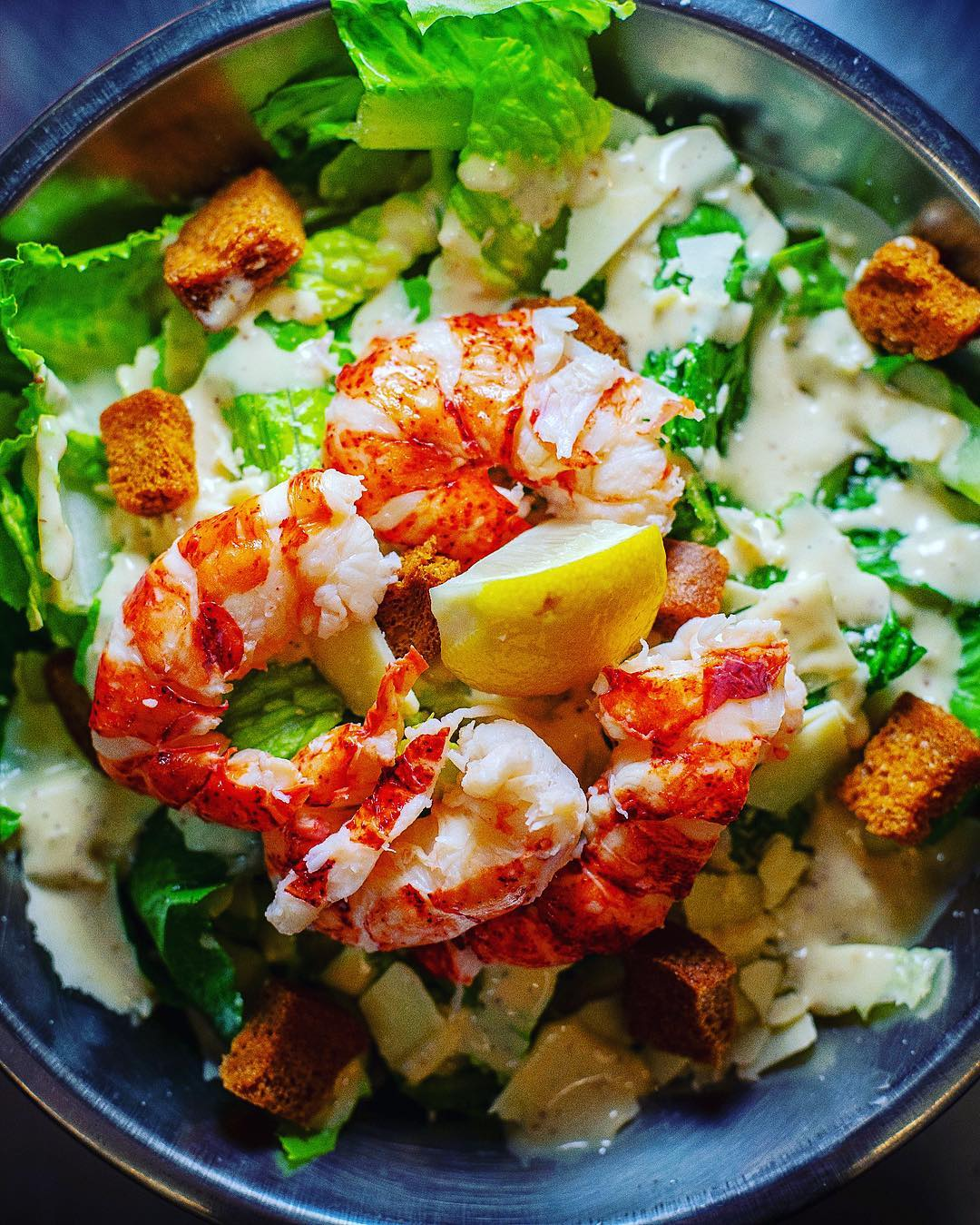 fresh shrimp with lemon wedge on leafy salad