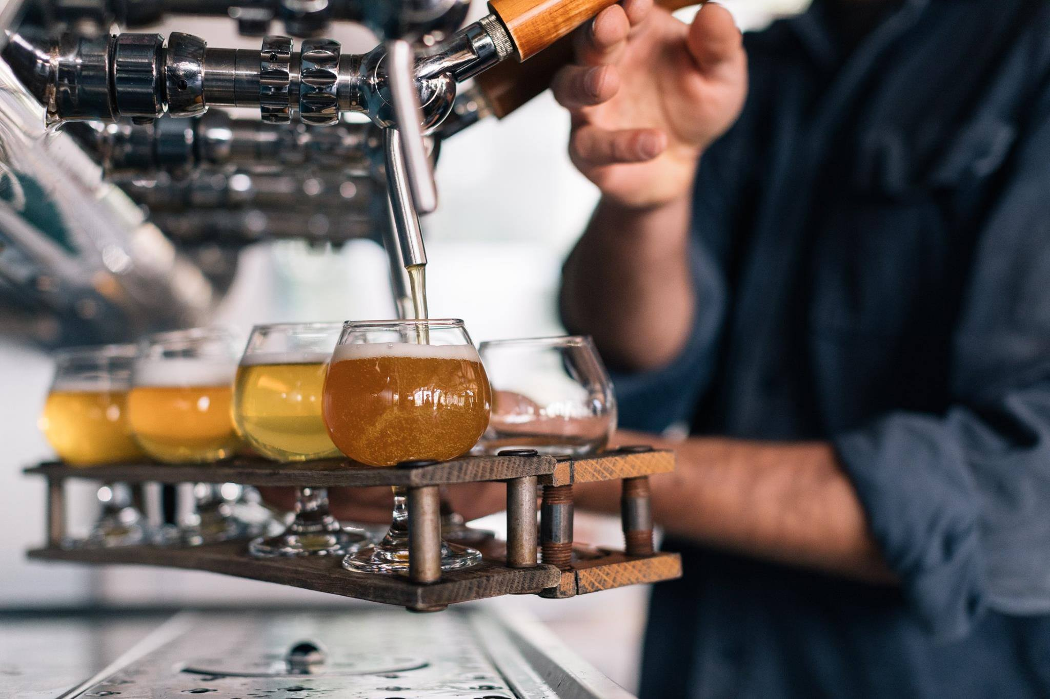 flights of Allagash beer being poured